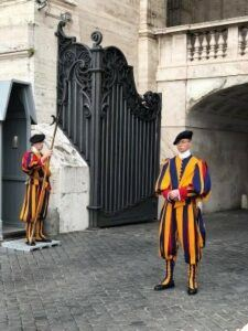 Illustration of Swiss guards in colorful gold and purple garb, guarding the Vatican